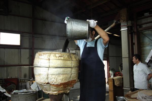 熱した菜種油を絞り器に入れる